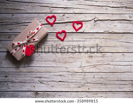 valentine gift box and red heart shape tag on wooden board - stock photo