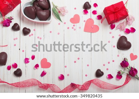 valentine gift box and red heart shapes on white wooden board - stock photo