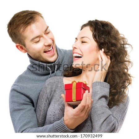 Valentine Gift. Happy Young Couple with Valentine's Day Present isolated on a White background. Happy Man giving a gift to his Girlfriend. Holiday - stock photo
