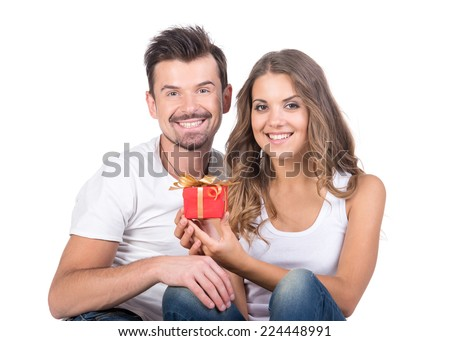 Valentine gift. Happy young couple with Valentine's Day present isolated on a white background. Happy man giving a gift to his girlfriend. Holiday