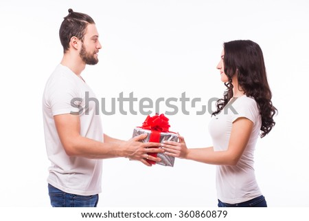 Valentine gift. Happy young couple with Valentine's Day present isolated on a white background. Happy man giving a gift to his girlfriend hand to hand. He look at she. Holiday - stock photo