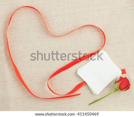 Valentine, greeting card with red little rose and red ribbon in the shape of a heart. On the cloth background. Space for your text. Handmade natural concept - stock photo