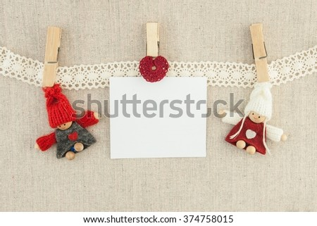 Valentine, greeting card. Wooden pins,  knitted loving couple man and woman, red heart,  lettering happy valentine's day hanging on a clothesline. On the cloth background - stock photo