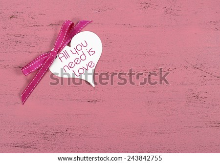 Valentine greeting heart shape gift tag with All You Need Is Love sample text on pink wood table. - stock photo