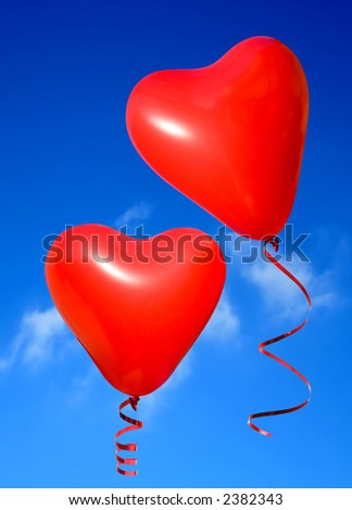 Valentine heart balloons against blue sky background.
