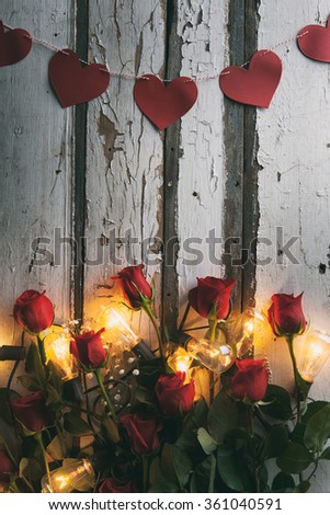 Valentine: Heart Banner Above Red Roses And Light Bulbs