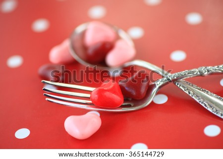 Valentine heart candies on silverware on a red and white polka dot background - stock photo