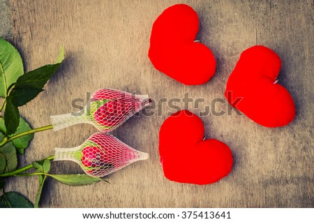 Valentine love symbol with two roses on a wooden board old look - stock photo