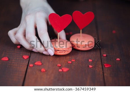 valentine macaroons on wooden table and girl hand taking one - stock photo