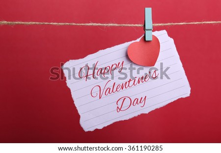Valentine note paper with red heart and Happy Valentine's Day text hanging on line against red background. - stock photo