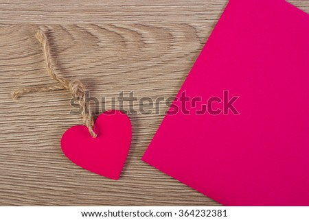 Valentine pink wooden heart with twine and love letter in envelope on wooden background, decoration for Valentines Day, symbol of love, copy space for text - stock photo