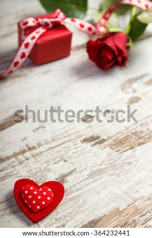 Valentine red heart, wrapped gift with ribbon and rose on old wooden background, decoration for Valentines Day, copy space for text - stock photo