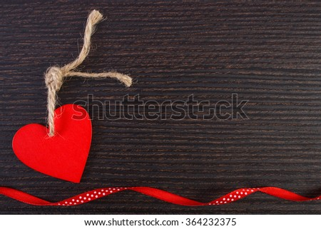 Valentine red wooden heart with twine and ribbon on wooden background, decoration for Valentines Day, symbol of love, copy space for text - stock photo