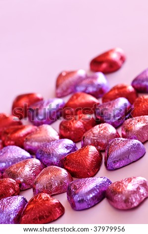 Valentine's chocolates wrapped in red and purple foil on white background