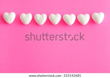 Valentine's Day. A row of white polystyrene hearts on a pink background - stock photo