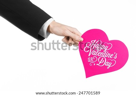 Valentine's Day and love theme: man's hand in a black suit holding a card in the form of a pink heart with the words Happy Valentine's Day, isolated on a white background in studio - stock photo