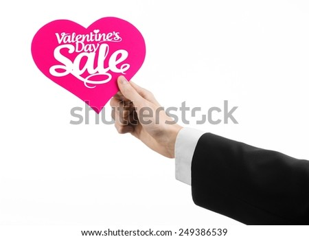 Valentine's Day and sale topic: Hand of a man in a black suit holding a card in the form of a pink heart with the word Sale isolated on white background in studio. - stock photo