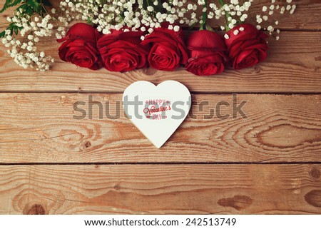 Valentine's day background with roses and heart shape on wooden table. View from above