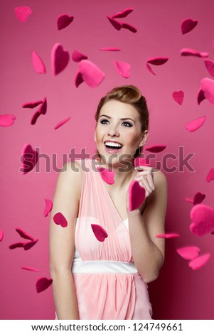 Valentine's day. Beautiful young woman with hearts falling around her. - stock photo