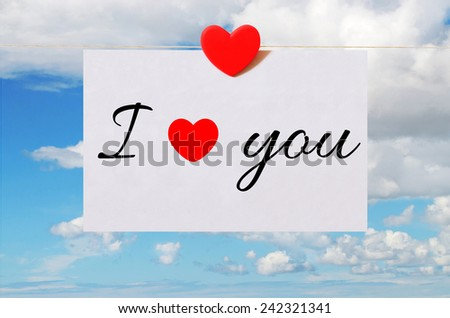 """Valentine's Day card """"I love you"""" with sky background and white sheet of paper held by heart shaped pin  - stock photo"""