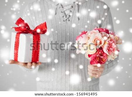 valentine's day, christmas, x-mas, winter, happiness concept - man holding bouquet of flowers and gift box - stock photo