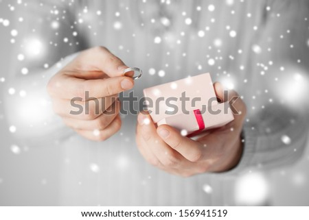 valentine's day, christmas, x-mas, winter, happiness concept - man holding wedding ring and gift box - stock photo