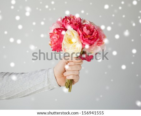 valentine's day, christmas, x-mas, winter, happiness concept - young man holding bouquet of flowers - stock photo