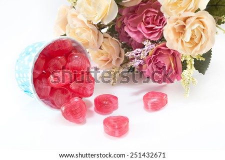 Valentine's Day Closeup of Candy, Foil wrapped chocolate hearts, Ribbon, Rose Valentines hearts on a white background - stock photo