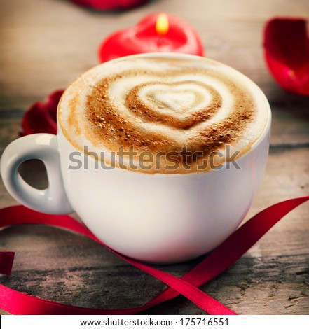 Valentine's Day Coffee with heart on foam. Heart drawing on cappuccino or latte art coffee. Love. Valentine art design. Coffee cup on a wooden table, heart shaped candle, rose petals and satin ribbon - stock photo