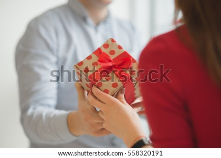 Valentine's Day concept. A loving couple celebrating Valentine's Day in the restaurant. Lovers give each other gifts