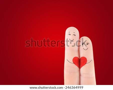 Valentine's Day concept - a man and a woman couple hold on the red heart, painted at fingers against red background - stock photo