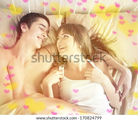 Valentine's day concept. Portrait of a happy young couple having fun on the bed  - stock photo