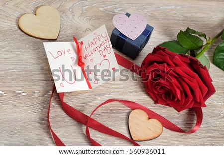 Valentine's day concept with crafted hearts, hand write love message and red rose on wooden background