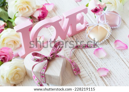 "Valentine's day concept with gift box, letters ""love"" and flowers on old vintage wooden background."