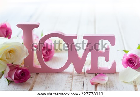"Valentine's day concept with letters ""love"" and flowers on old vintage wooden background - stock photo"