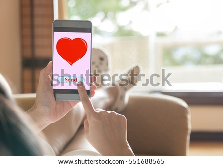 Valentine's Day concept.  Woman using mobile smart phones to send pictures red heart to the man she loves.