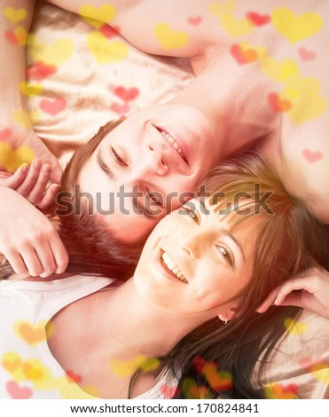 Valentine's day concept. Young happy couple in bed  - stock photo