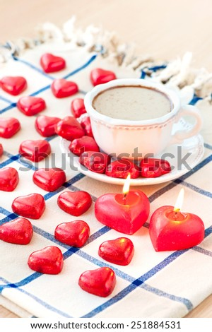 Valentine's day cup of coffee with many heart shaped sweet chocolates and candles. Celebration surprise. - stock photo