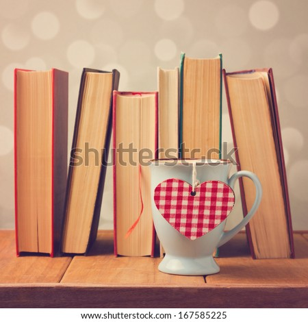 Valentine's day cup with heart shape and books - stock photo