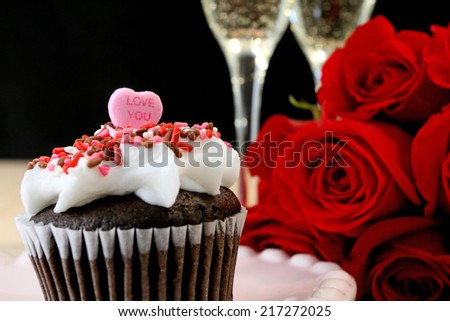 Valentine's day cupcake with love you candy heart, red roses, and champagne. - stock photo