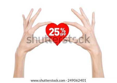 Valentine's Day discounts topic: Hand holding a card in the form of a red heart with a discount of 25% on an isolated white background in studio - stock photo