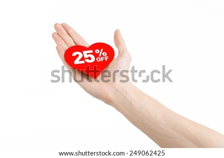 Valentine's Day discounts topic: Hand holding a card in the form of a red heart with a discount of 25% on an isolated white background in studio