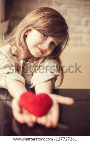 Valentine's Day -  dreaming cute child with red Heart in hands. Series of photos - stock photo