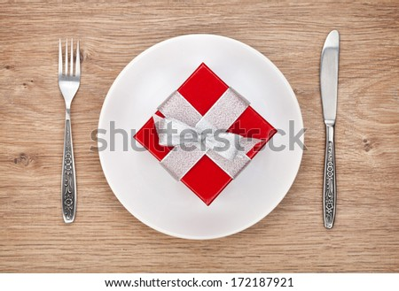 Valentine's day gift box on plate and silverware. View from above on wooden table background
