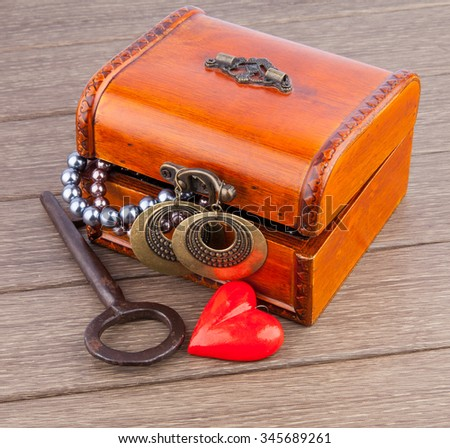 Valentine's Day gift chest with treasure and heart decoration on wooden - stock photo
