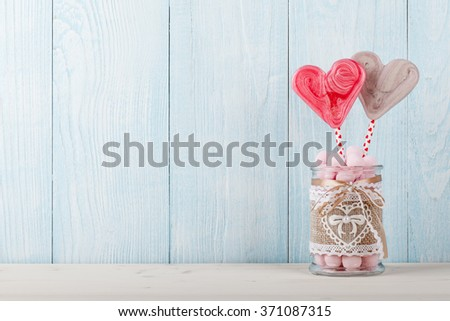 Valentine's Day heart shaped candy and pink candy balls in the glass jar on blue wooden background - stock photo