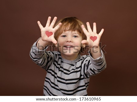 Valentine's Day Love Theme: Child Showing Picture of Hearts on Palms of his Hands - stock photo