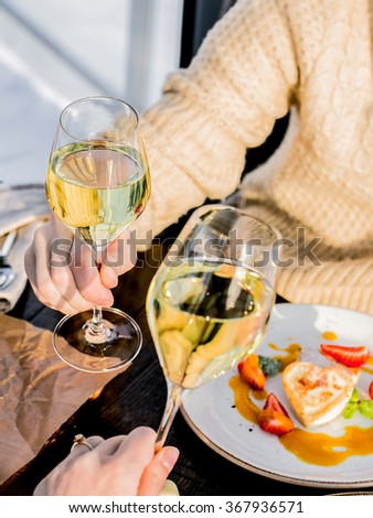 Valentine's Day Lover Breakfast with champaign and heart-shaped treats and strawberries, open-face sandwiches, male hand holding a glass, vertical