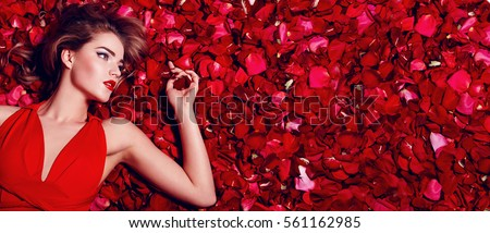 Valentine's Day. Loving girl. The girl in a red dress lying on the floor in the petals of red roses. Background of red rose petals. Red lipstick on the lips from the beautiful girl.