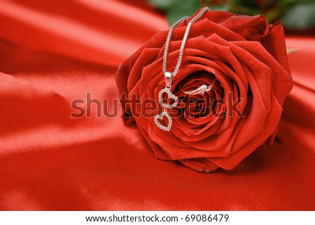 Valentine's day necklace with two hearts pendant and a ring on red rose. - stock photo